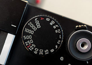 Shutter time  The white line on the camera body indicates what the shutter wheel is set to. It is not the mark (as in the old days) of where the film plane is.