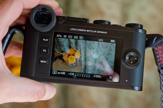 The Leica CL has a touch screen. If you press the button in the center to the right of the screen, you change the view of information on the screen, from no text at all, to all information. On this screen you can see (clockwise from top left) that the auto focus is set to AF Single point, the white balance is set to Auto White Balance, the camera shoots in DNG format only, the light metering symbol tell that the calea is set to Multi Field, and the next synbol of multiple frames tell it is set to Continious shooting. The look of the preview (and JPG files if the camera takes JPG files at the same time as DNG, is set to STD (standard; and not saturated, monochrome or other). Battery synbol tells the battery is full.  From left to right in the bottom, the mode is set to Aperture priority, the ISO is set to 400, the lens is set to f/2.8. The exposure white dot in the middle of the scale shows that I am not adjusting the exposure. 1/200 sec is the exposure time, and I have 1K (1,000) pictures left on the memory card.
