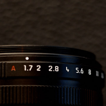 Aperture ring  The maximum aperture of the Leica Q2 lens is f/1.7. In my opinion, that's where the aperture should be set so as to utilize the full potential of bokeh and depth of field.  The aperture can be turned to more depth of field by going to f/5.6 or such, for example when doing macro.  The aperture ring can also be locked in A (Auto) which will make the Leica Q2 determine the aperture, not based on depth of field, but as a measure to control light.