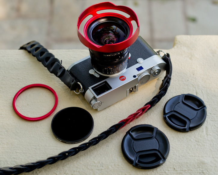 The 2114OUS ventilated shade for the Leica 21mm Summilux-M ASPH f/1.4 comes with a front ring for mounting the Series VIII filter, as well as two lens caps: One that fits the shade without filter, and one that fits the shade when the filter ring is mounted.
