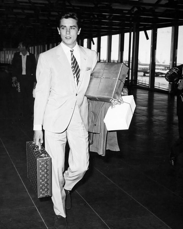 Alain Delon in the airport. The classic way of traveling, without wheels and shoulder straps