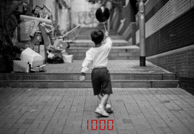 The viewfinder displays the suggested shutter time the camera's light meter came up with. Here it's 1/1000 of a second. Boy playing in Hong Kong. Leica M-D 262 with Leica 50mm Noctilux-M ASPH f/0.95. © 2016 Thorsten Overgaard.