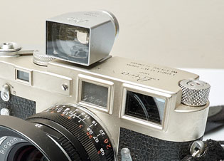 Leica M3 (1954) with a super-wide optical viewfinder on top of the camera so as to see what the frame will be. Built-in to the camera itself is the optical viewfinder (right) with a distance-finder image provided from the small eye to the left.