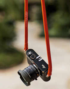"125cm x 15mm x 3mm Black Calfskin Camera Strap with orange edges. Inscription on the inside, ""Always Wear A Camera""."