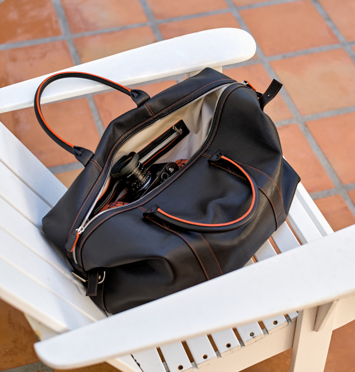 A travel bag, for photographers. The Von Cuba 55 in black soft Italian calfskin on the outside, with handpainted orange edging, soft alcantara on the inside. Designed by Thorsten von Overgaard and Matteo Perin.