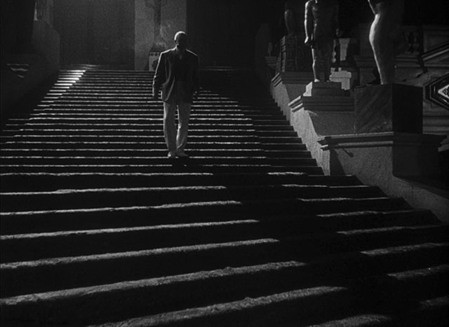 A strong light source from behind (top left outside the frame) adds long shadows and edge light that defines the person, the stairs and the statues. Citizen Kane (1941, cinematography by Gregg Toland, directed by Orson Welles).