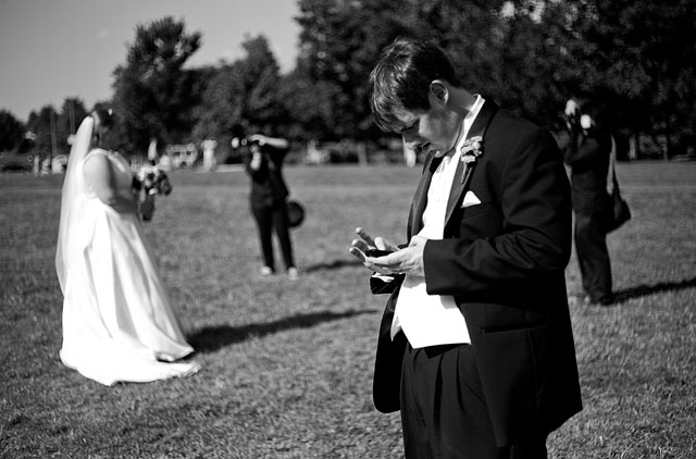 A bride fighting with her white balance appearance in Philadelphia in July 2011 while her new husband is updating his relationship-status on Facebook. © Thorsten Overgaard.