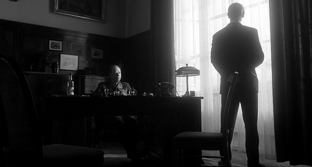 All this darkness, the magnificent position of the silhouette in the window ... and the usual slight overflow of light you often see in Spielberg scenes. Schindler's List (1993, directed by Steven Spielberg, cinematography by Janusz Kaminski).