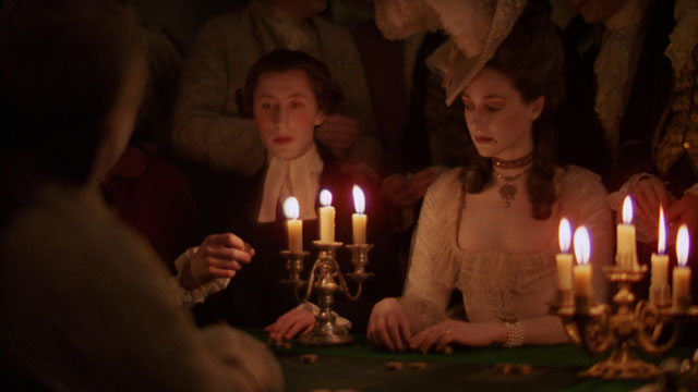 Stanley Kubrick's candlelight lit scene in Barry Lyndon is famous for being shot using only candlelights and special-made Zeiss 50mm f/0.7 lenses. He might have adjusted the color slightly with filters, but else it is close to the actual look which is not because it is low light, but because the light from candles is warm light.